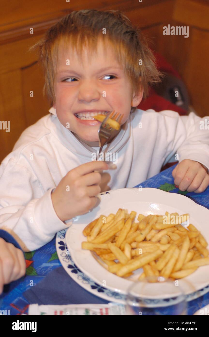 Sechs Jahre alten Jungen Essen Pommes frittes Stockbild