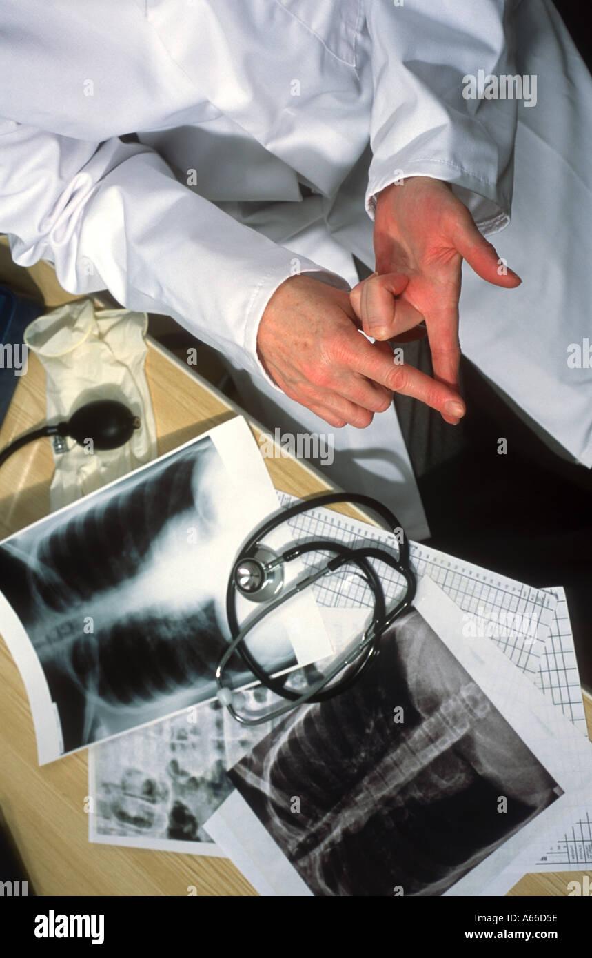 Arzt in der Chirurgie mit Brust Röntgenaufnahmen und Stethoskop auf dem Schreibtisch bespricht medizinische Stockbild