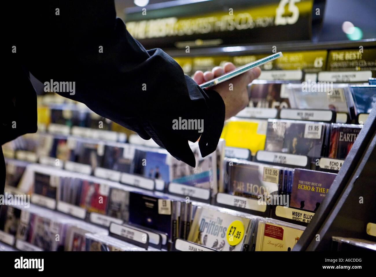 Mann fallen nimmt CD Regal im HMV am Piccadilly Circus CD-Verkäufe wie Online-Musik-erhöhen Downloads Stockbild