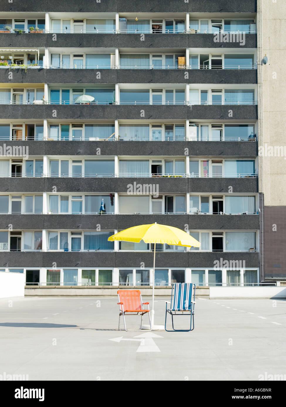 Liegestühle und Sonnenschirm außerhalb Mehrfamilienhaus Stockbild