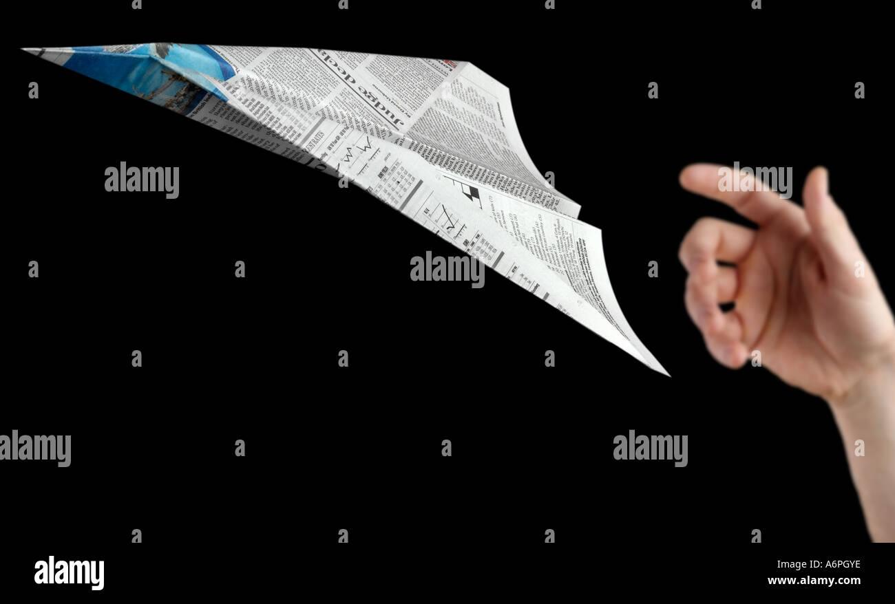 Eine Person wirft einen Papierflieger aus Zeitung gemacht Stockfoto