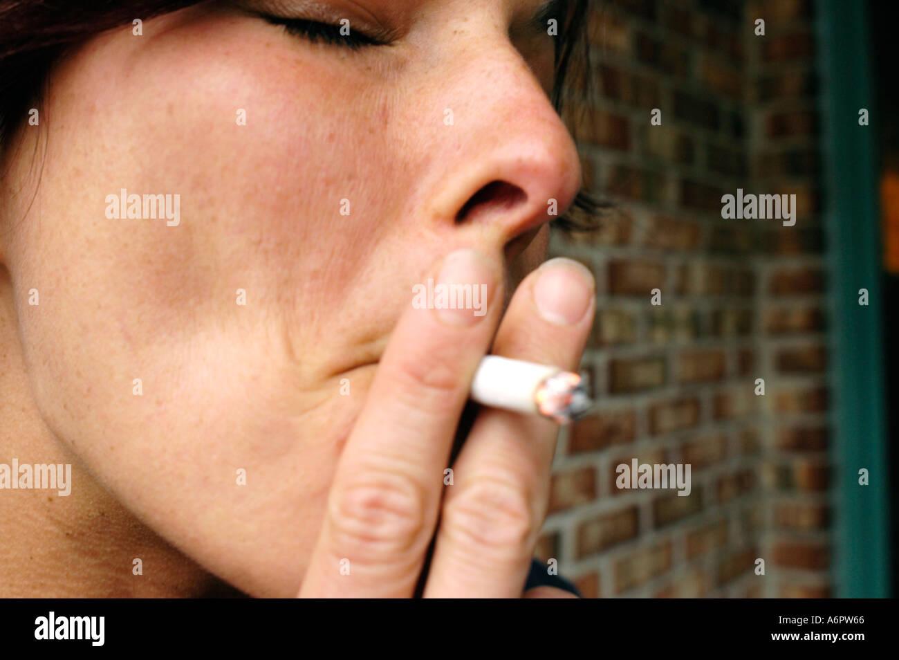 Junge Frau mit dunklen Haaren Rauchen einer Zigarette 30 Stockbild