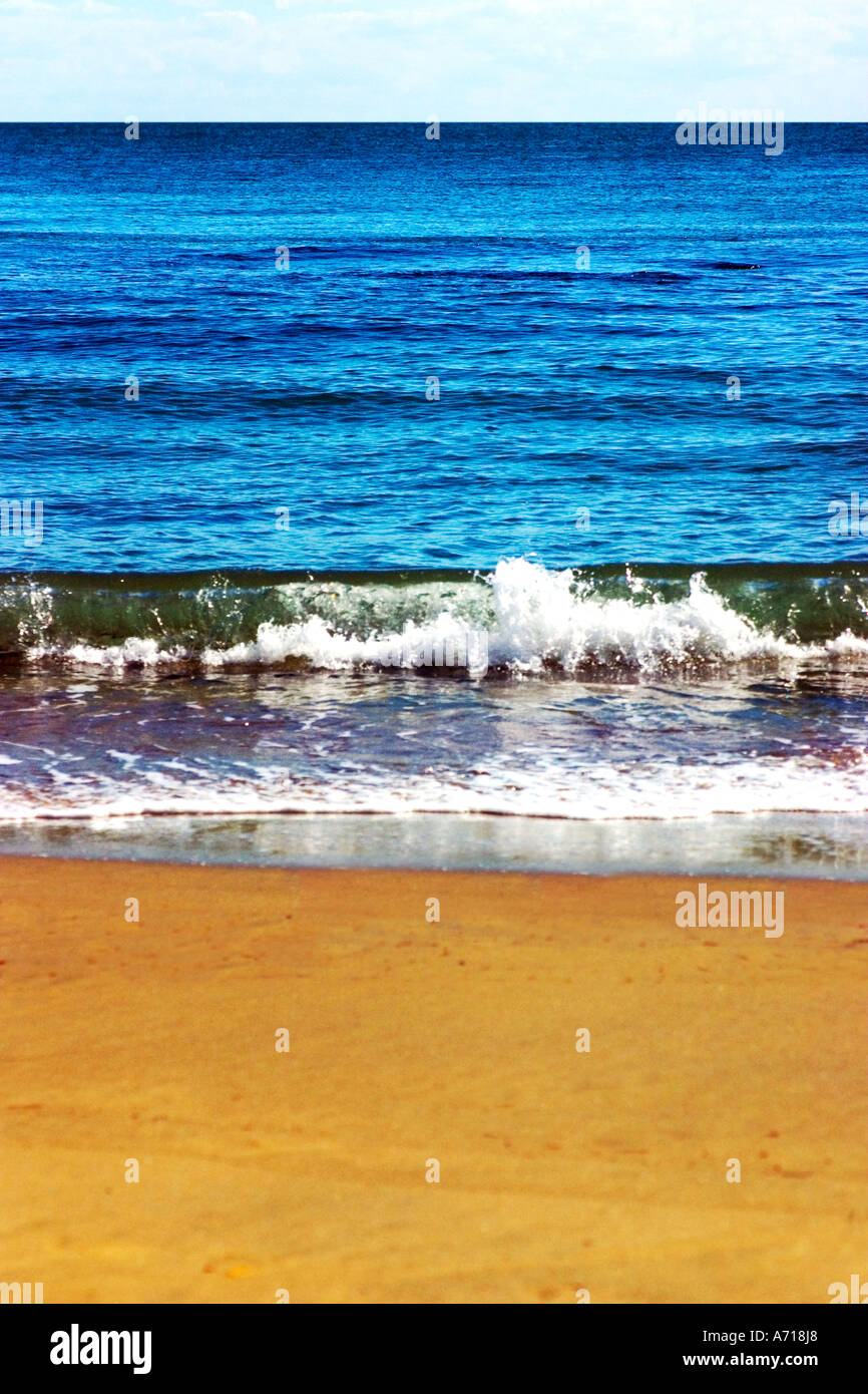 Sanfte Wellen auf einer sandigen Küste. Stockbild