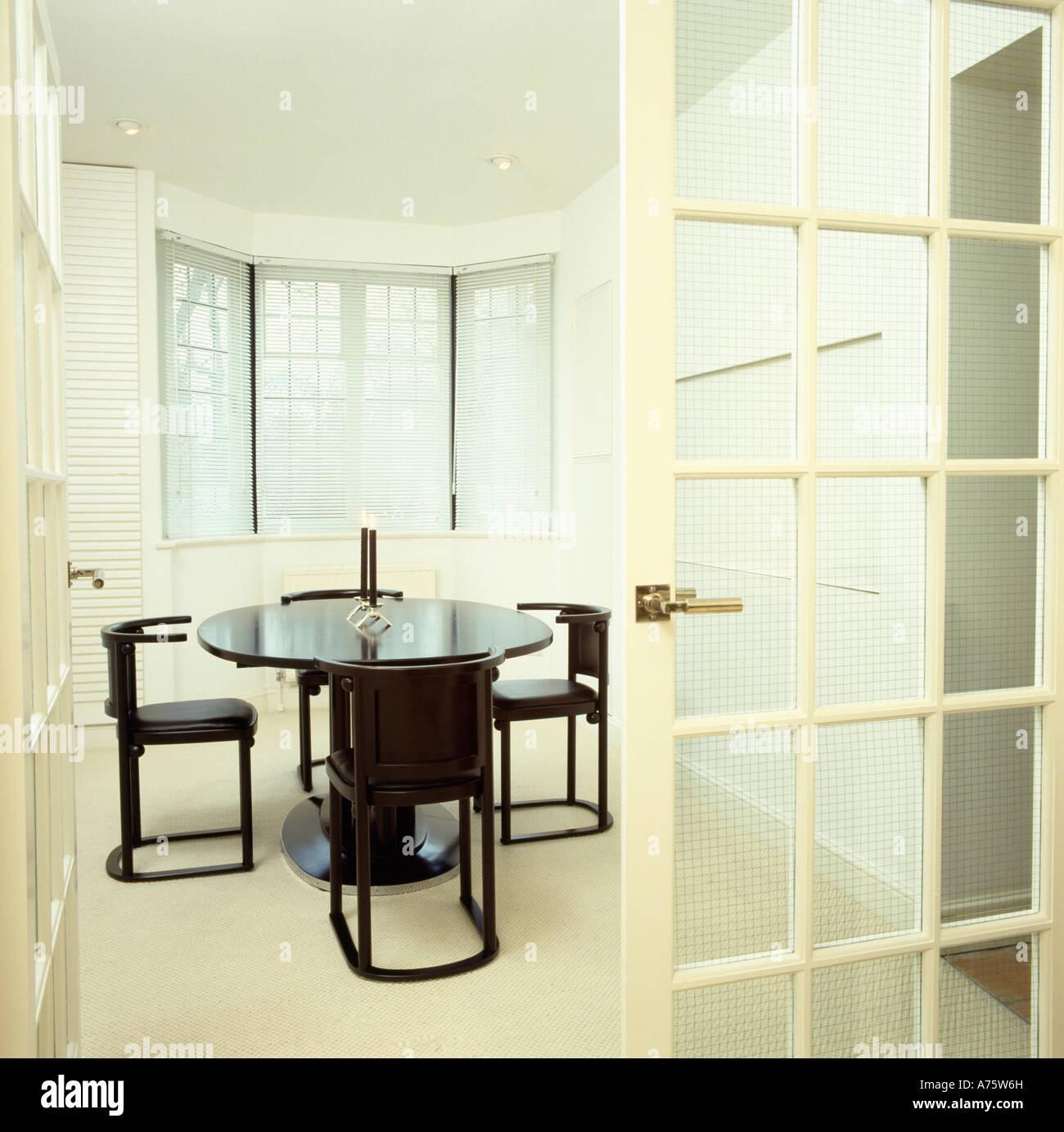 verglaste t r offen f r moderne wei e stadt esszimmer mit schwarzen tisch und st hlen stockfoto. Black Bedroom Furniture Sets. Home Design Ideas