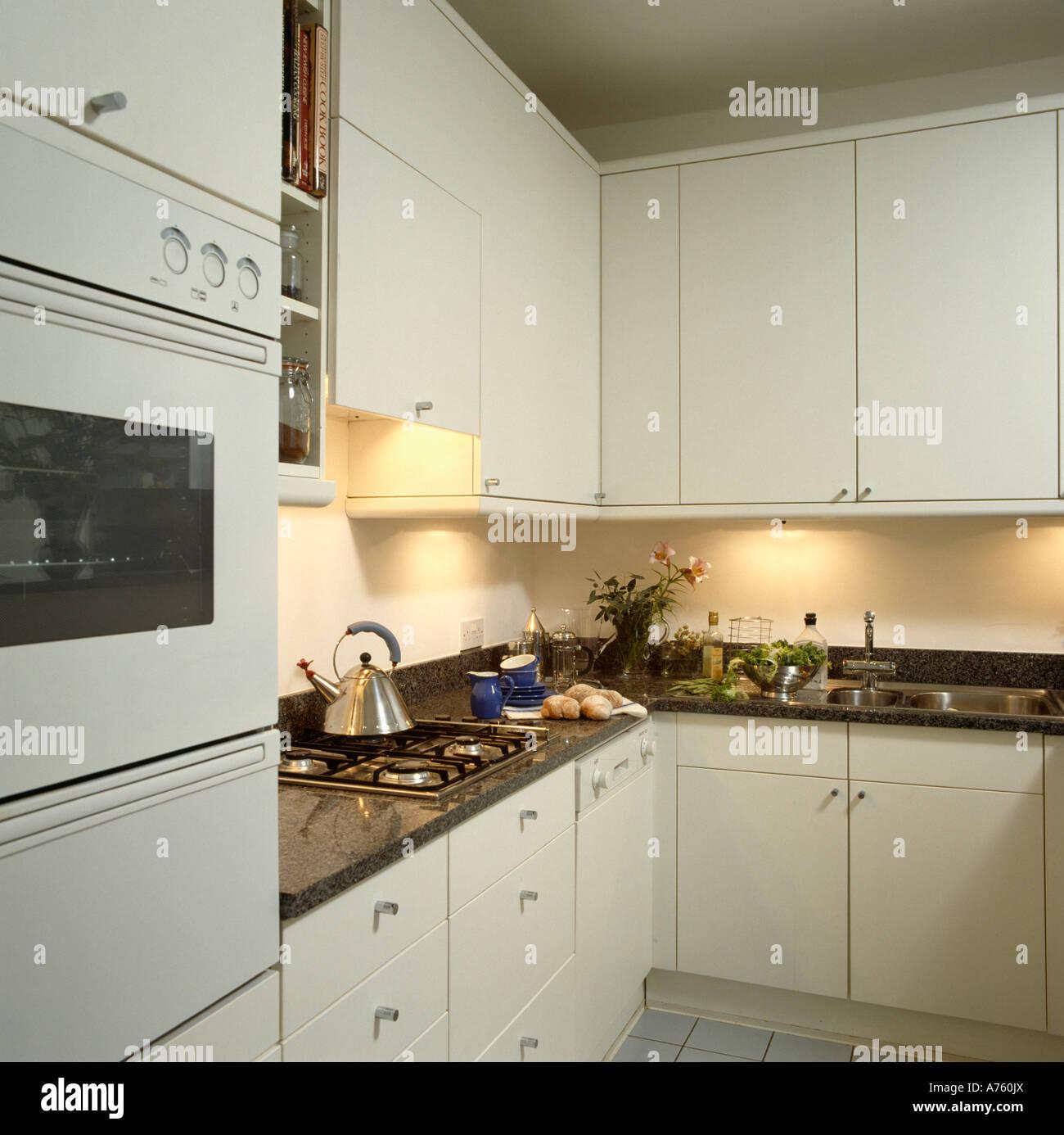 Kleine weiße Küche mit Wand-Ofen und schwarze Arbeitsplatten mit ...