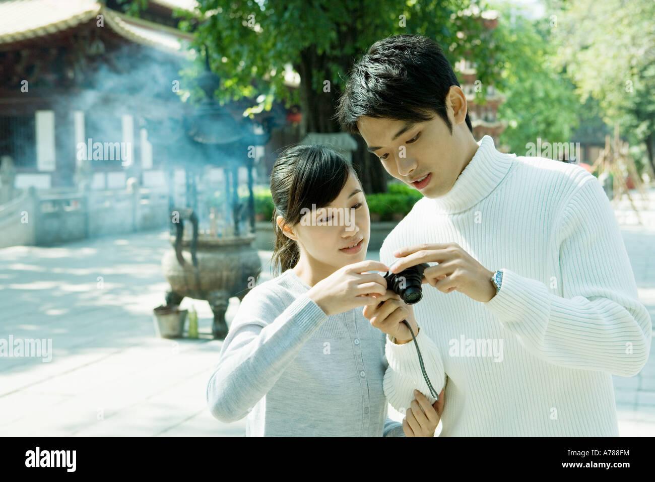 Paar auf der Suche in die digitale Kamera, Tempel im Hintergrund Stockbild