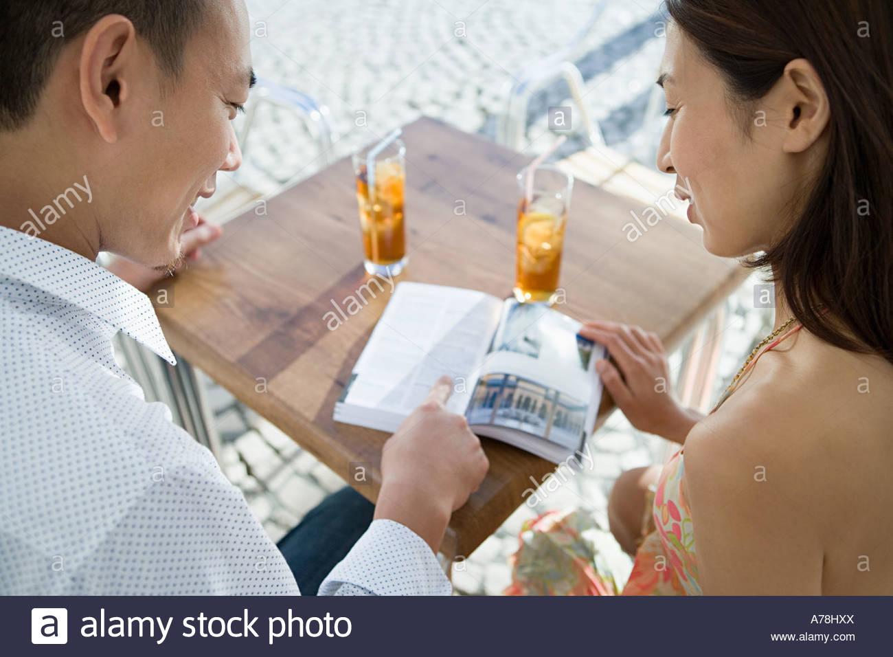 Paar auf der Suche im Reiseführer Stockbild