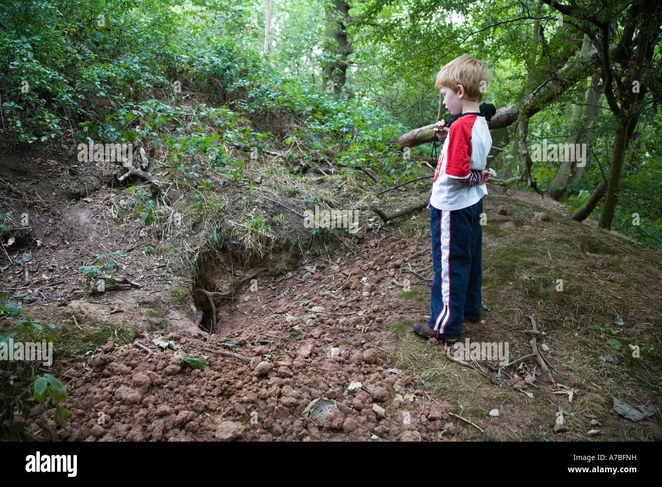 Junge Junge stand auf Hügel außerhalb eines Dachs sett Stockfoto