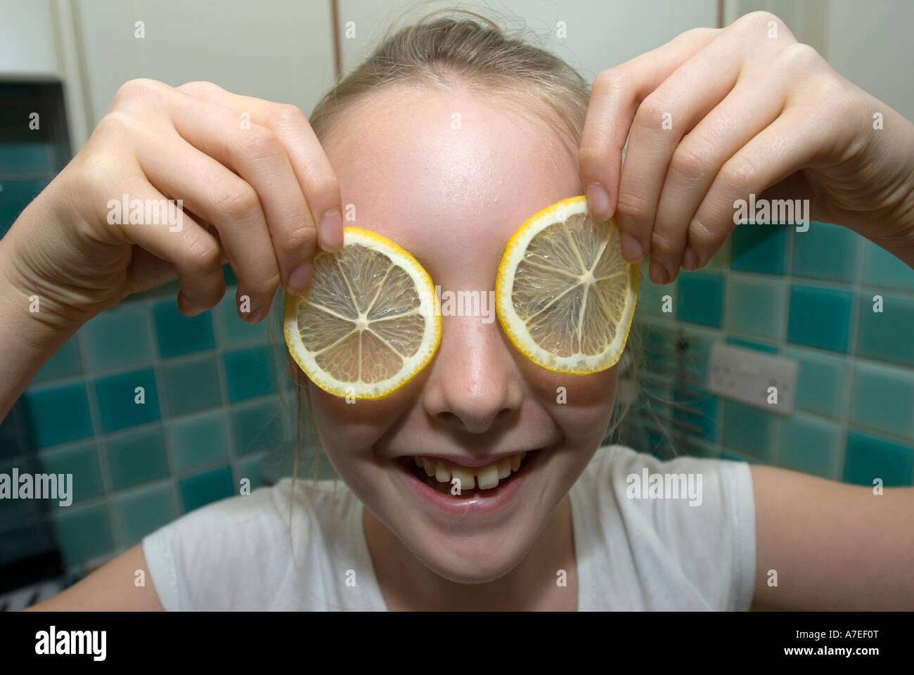Junges Mädchen lacht, als sie vor ihrem Gesicht für Augen UK Zitronenscheiben legt Stockbild