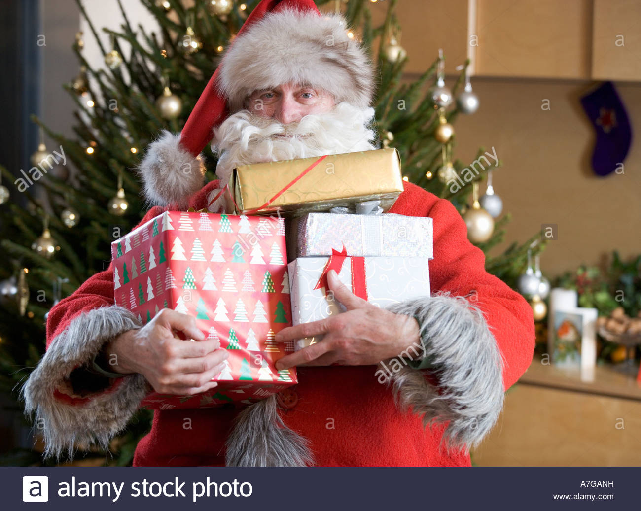 Nikolaus / Weihnachtsmann hält einen Haufen von Geschenken Stockbild