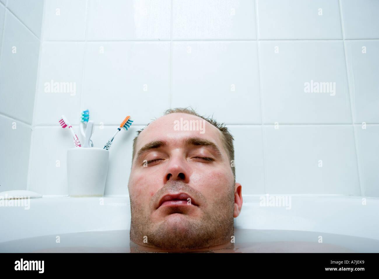 Kopf eines Mannes mit geschlossenen Augen und der Rest seines Körpers, mitten in der Badewanne Stockbild