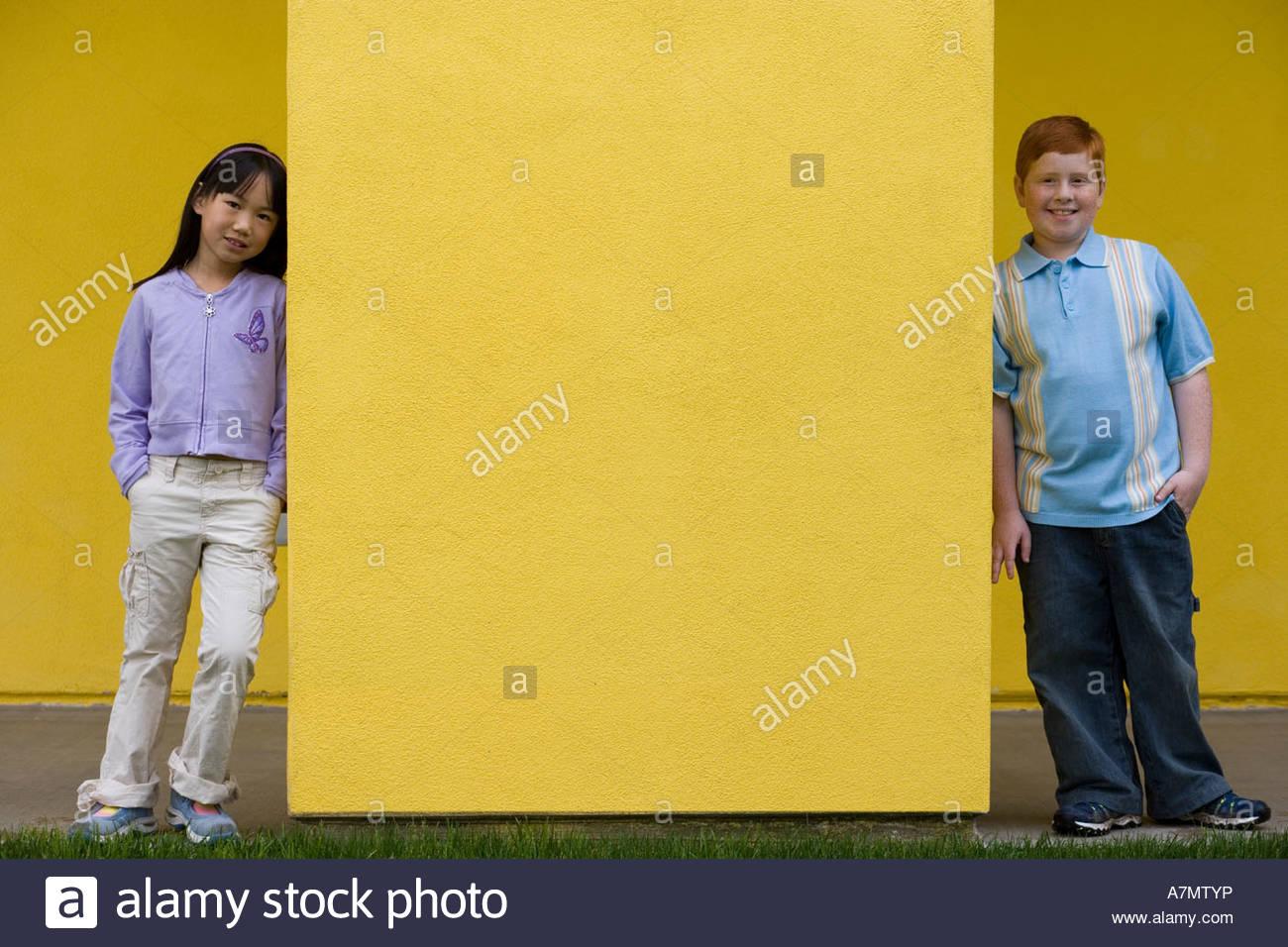 Jungen 10 12 und Mädchen 9 11 stehend an den entgegengesetzten Enden der gelben Wand lächelnd Vorderansicht Stockbild