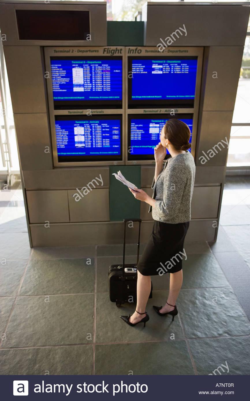 Geschäftsfrau, die Abfahrtszeiten im Flughafen-Lounge, die Ticket auf dem Bildschirm betrachten erhöht, Stockbild