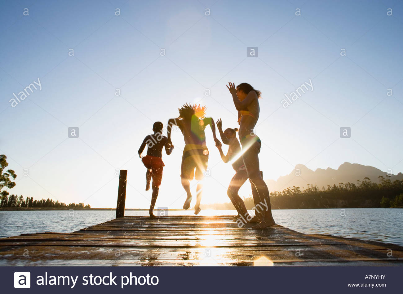 Familie in Badebekleidung entlang Steg springen in See bei Sonnenuntergang Rückansicht Oberfläche Ebene Stockbild