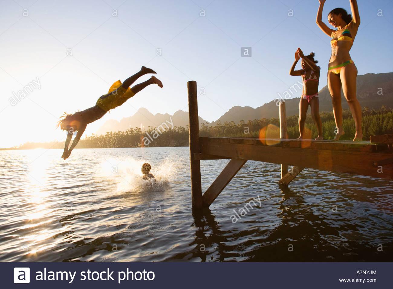 Vater und Sohn 8 10 in Badebekleidung tauchen ab Anlegestelle in See bei Sonnenuntergang Mutter und Tochter 7 9 Stockbild