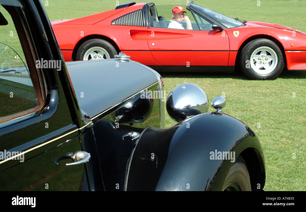 Alte schwarze Limosine gegenübergestellt mit roten Ferrari Stockbild