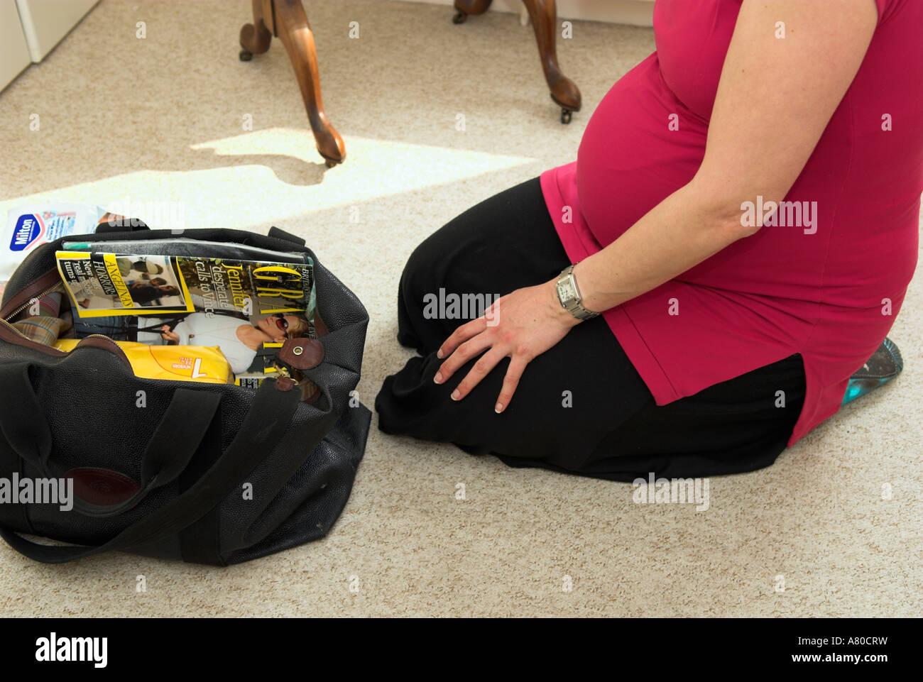 Fußboden Im Krankenhaus ~ Neun monate schwangere frau sitzen auf boden verpackung reisetasche