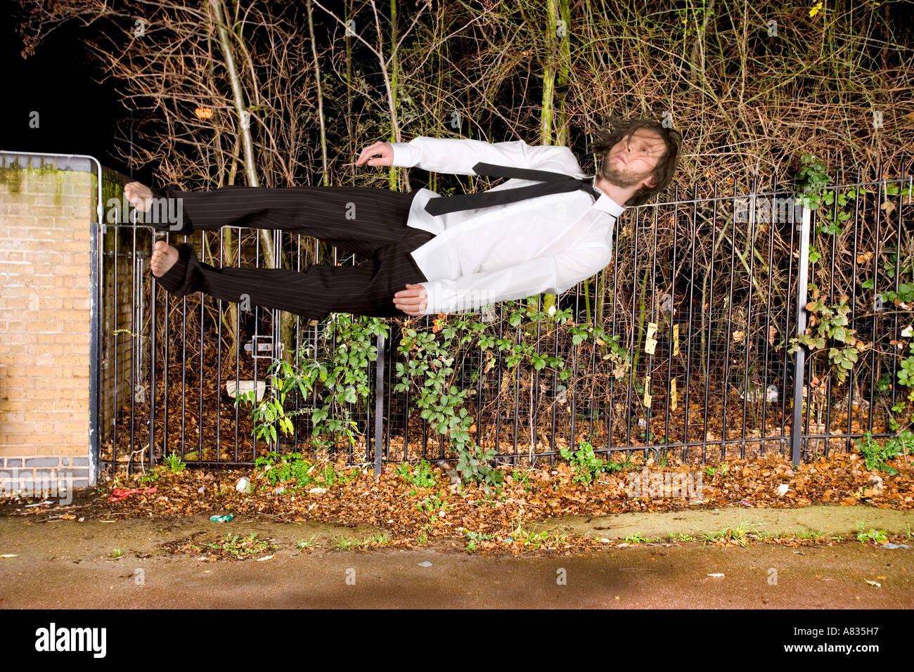 In der Luft Mann in Abendkleidung horizontal in einer verlassenen Gegend in der Nacht fallen. Stockfoto