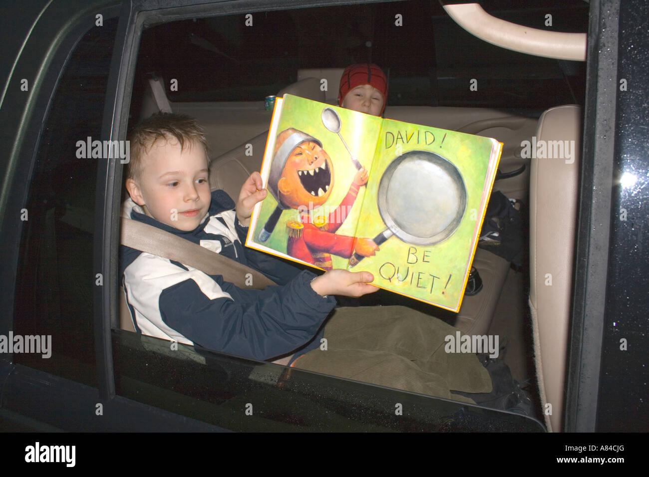 """Jungen Alter 7 hält David! ruhigen Buchseite im Auto zu sehen sein.  """"St. Paul"""" Minnesota USA Stockbild"""