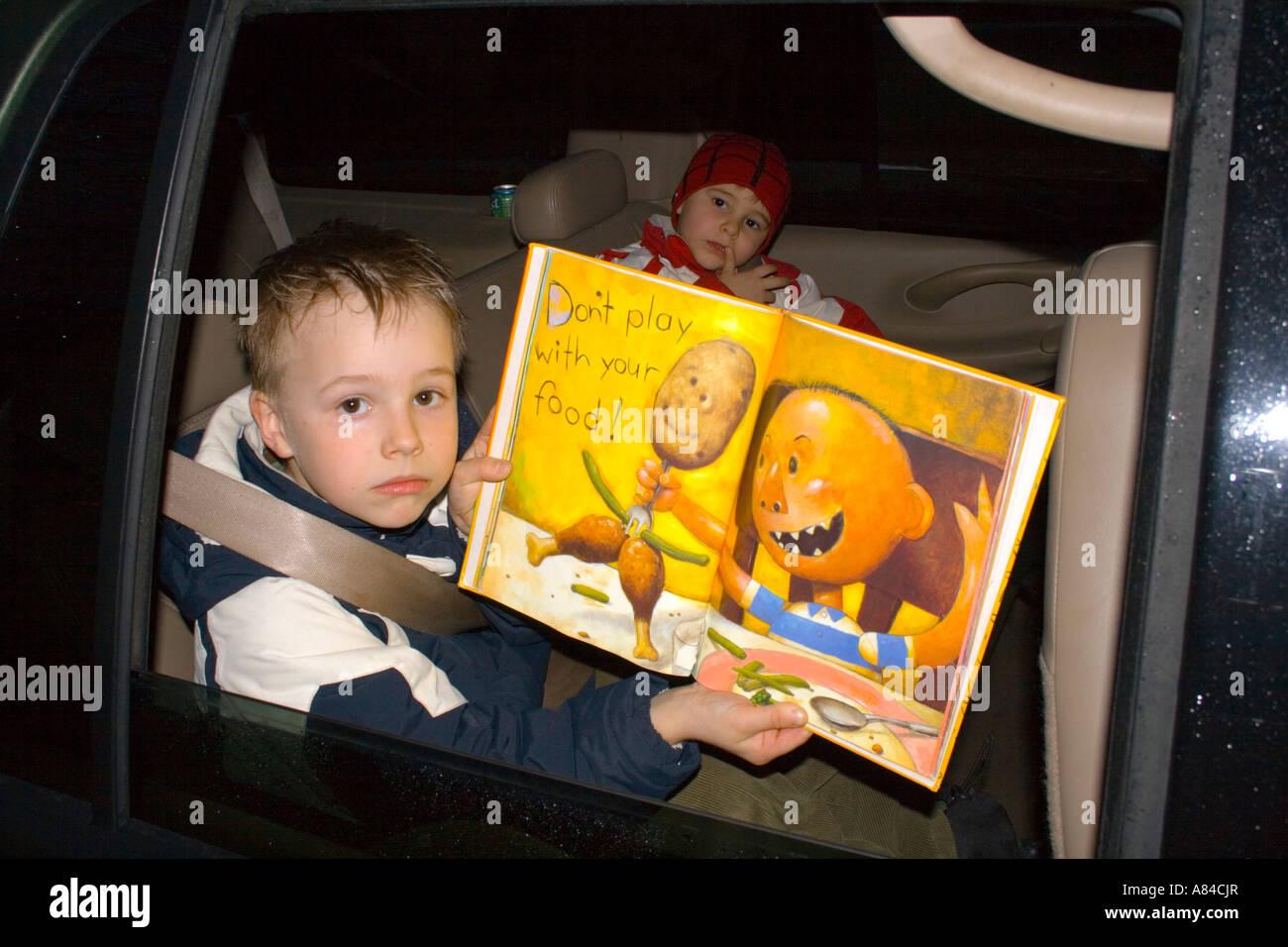 """Jungen Alter 7 hochhalten Spiel nicht mit Ihrer Seite """"Food-Buch"""" im Autofenster.  """"St. Paul"""" Stockbild"""