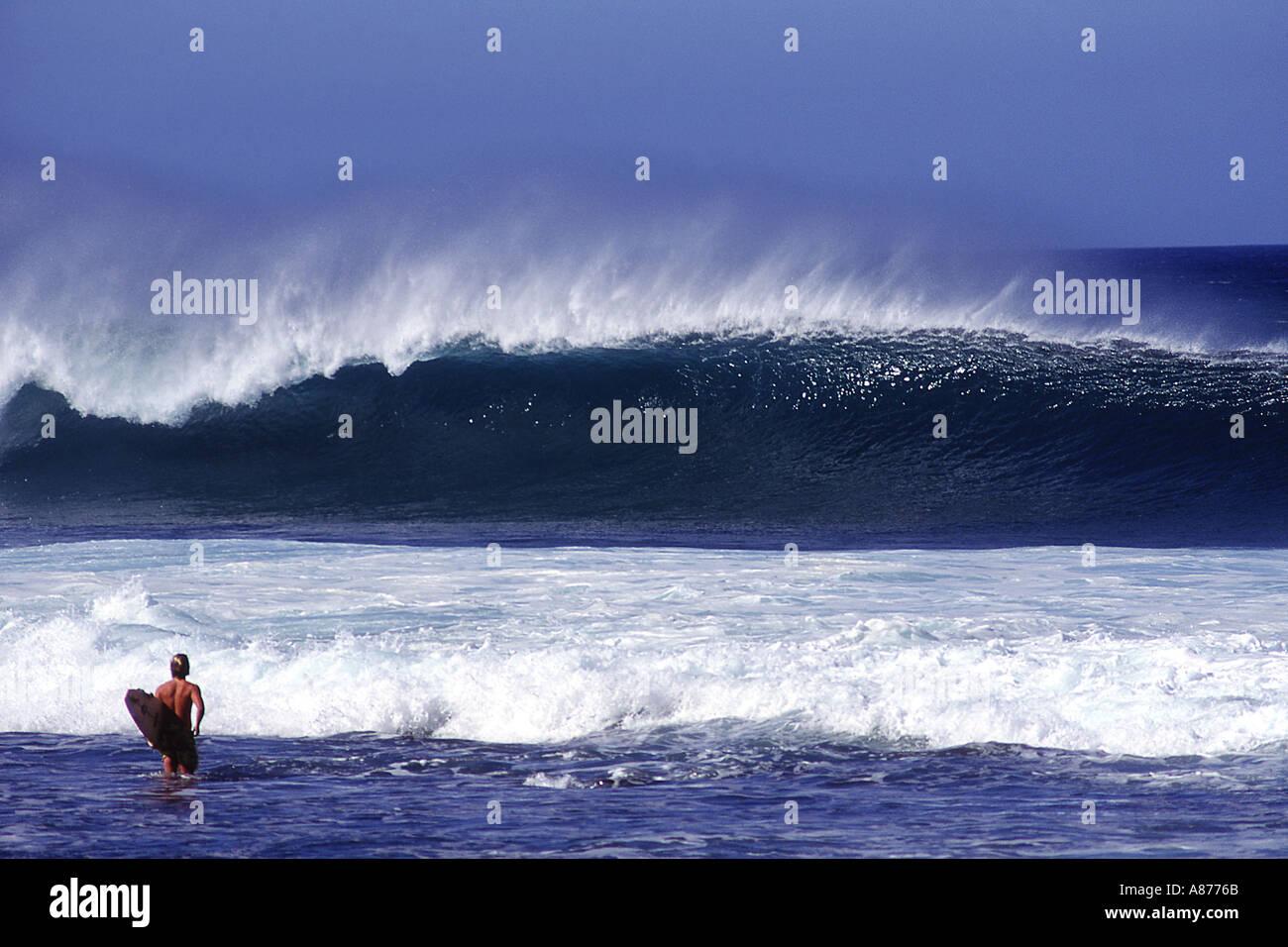 Eine tolle Welle stürzt wie ein Surfer hält eine Surf Board Spaziergänge in die glänzende blaue Wasser Stockfoto