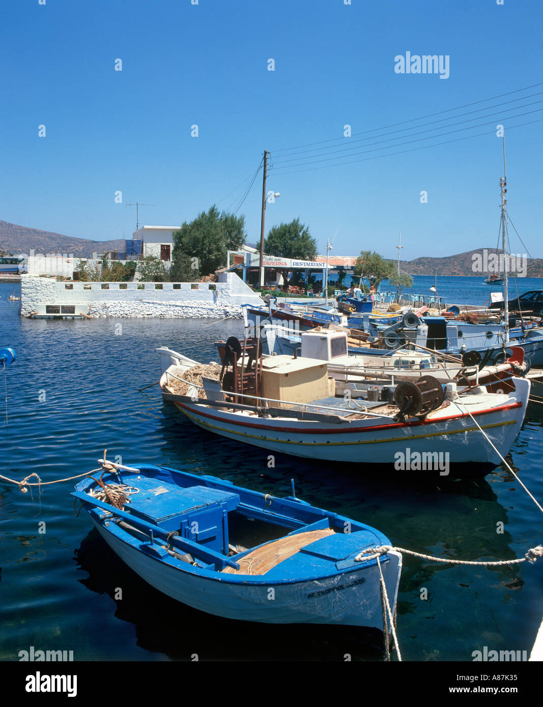 Angelboote/Fischerboote in den Hafen mit einer Taverne hinter Elounda, Kreta, Griechenland im Jahr 1993 Stockbild