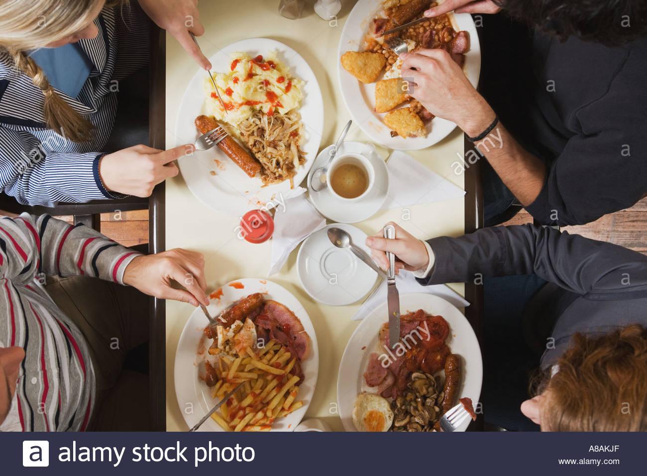 Vier Freunde Essen im café Stockbild