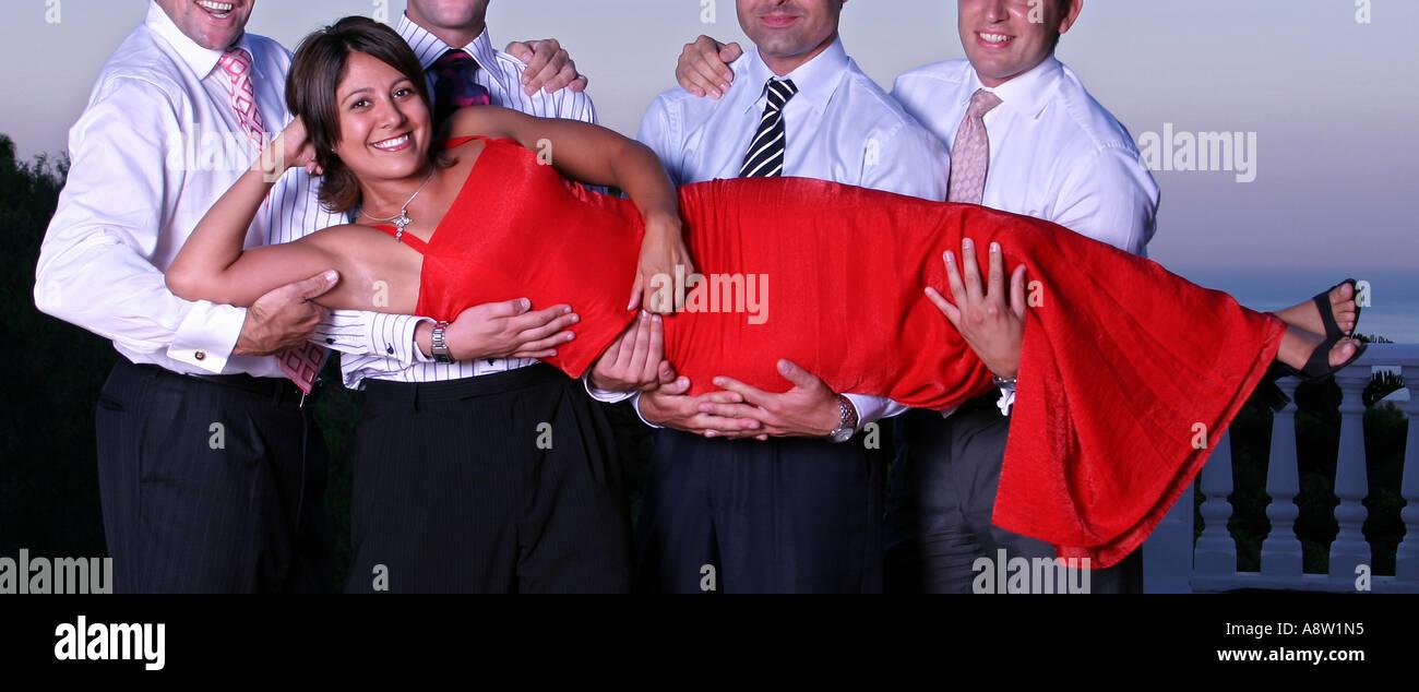 Smart wohlhabende junge Frau in einem roten Kleid von vier Männern ...