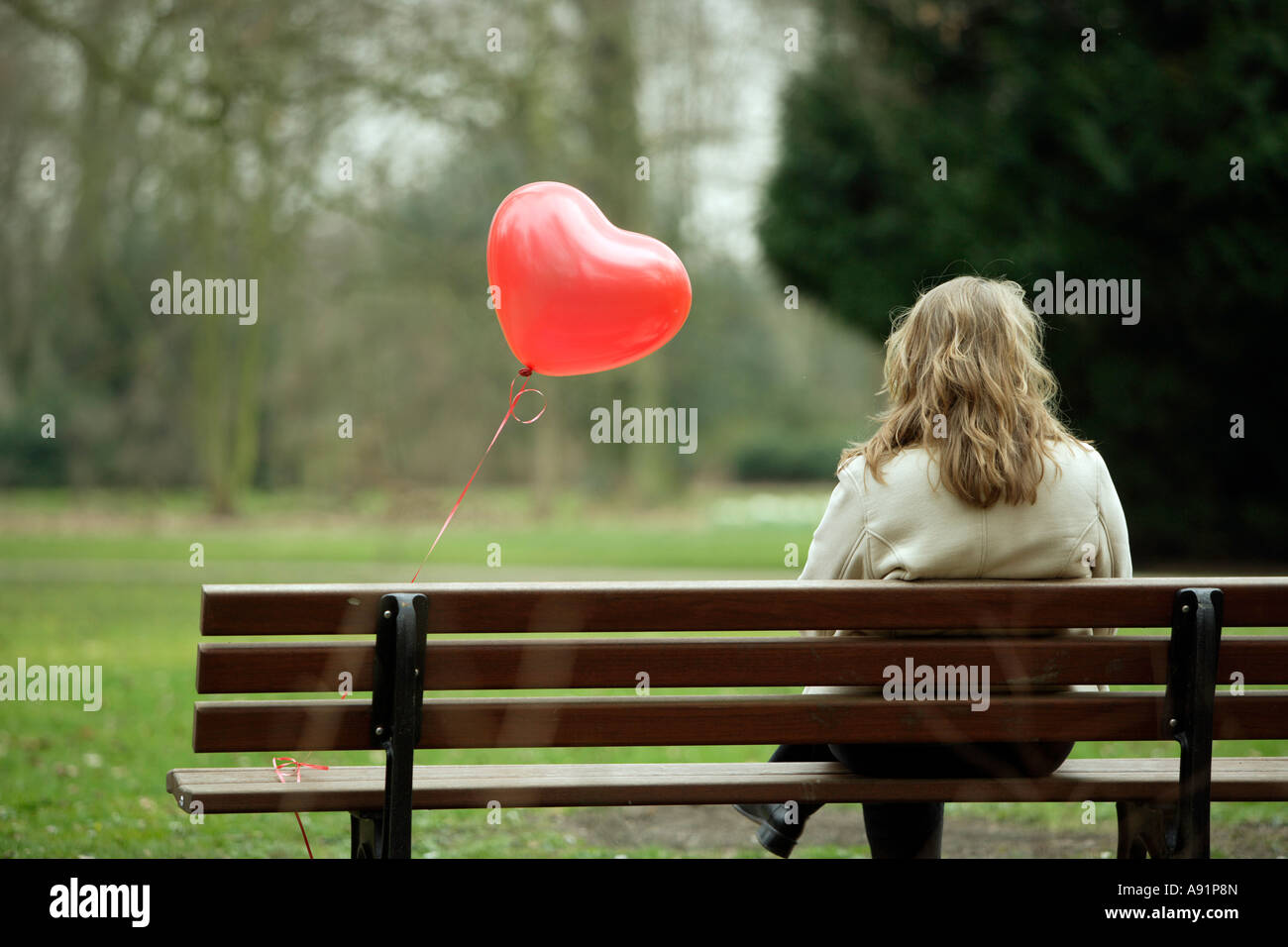 Eine junge Frau sitzt alleine auf einer Parkbank Stockbild