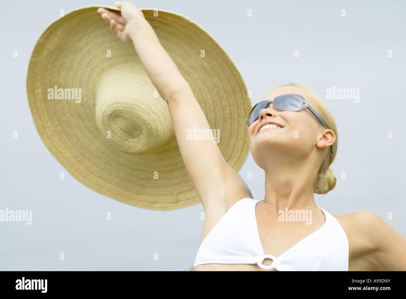 Junge Frau mit Sonnenbrille, Sonnenhut, Kopf und Schultern hochhalten Stockbild