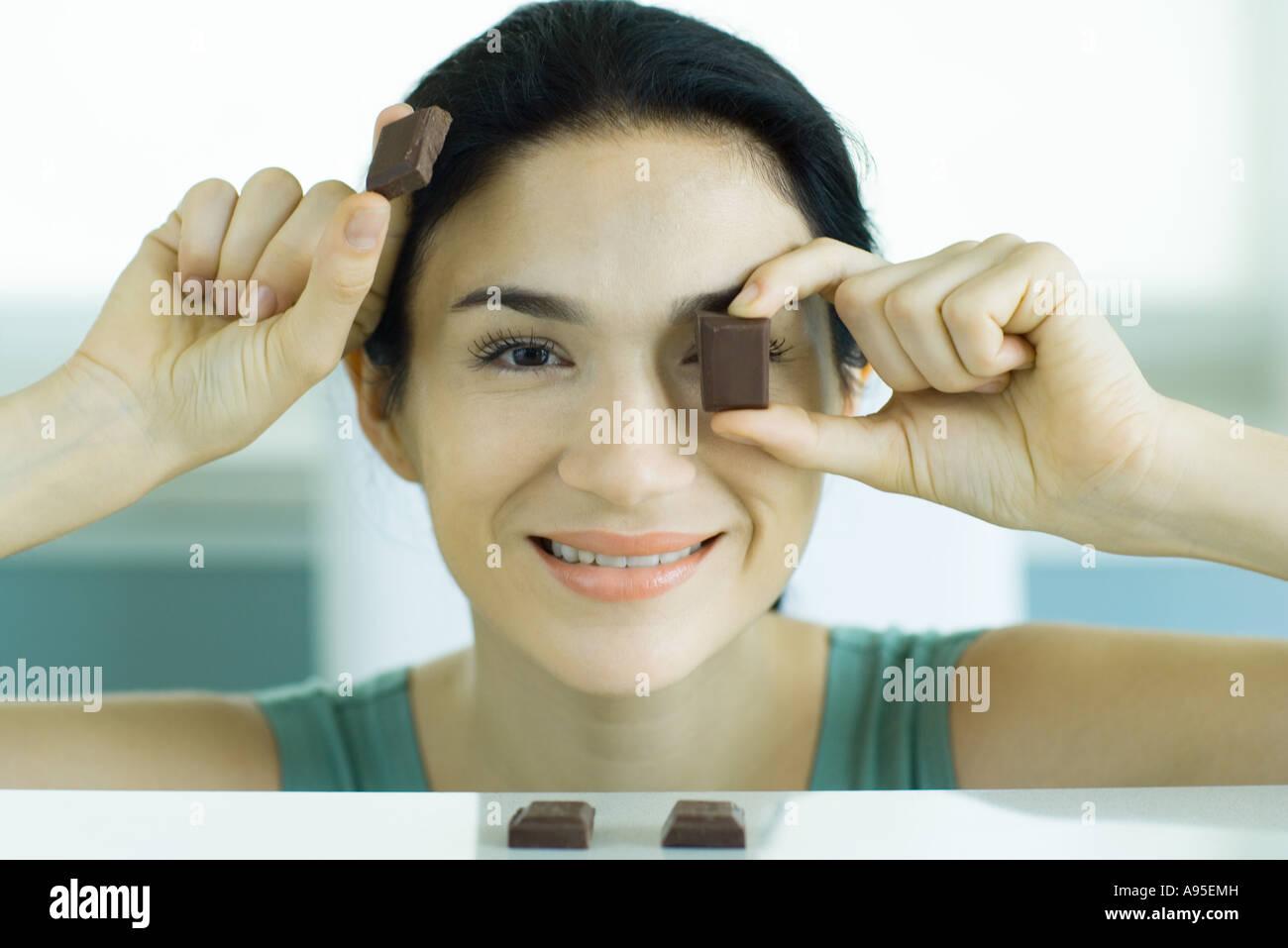 Frau hält sich Stücke von Schokolade Stockbild