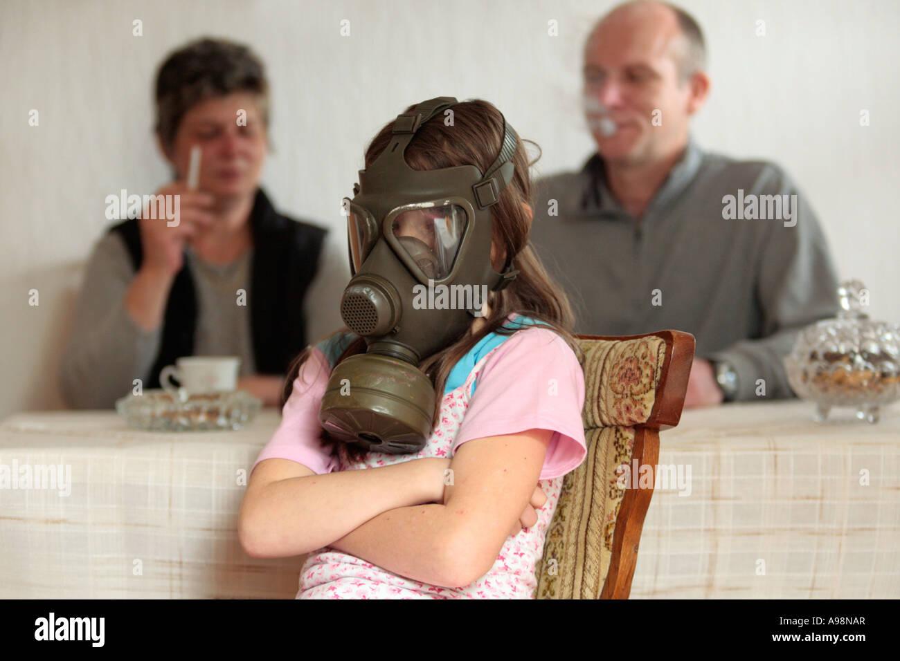 ein junges Mädchen ist demonstrativ eine Gasmaske tragen, weil ihre Eltern im Zimmer Rauchen Stockbild