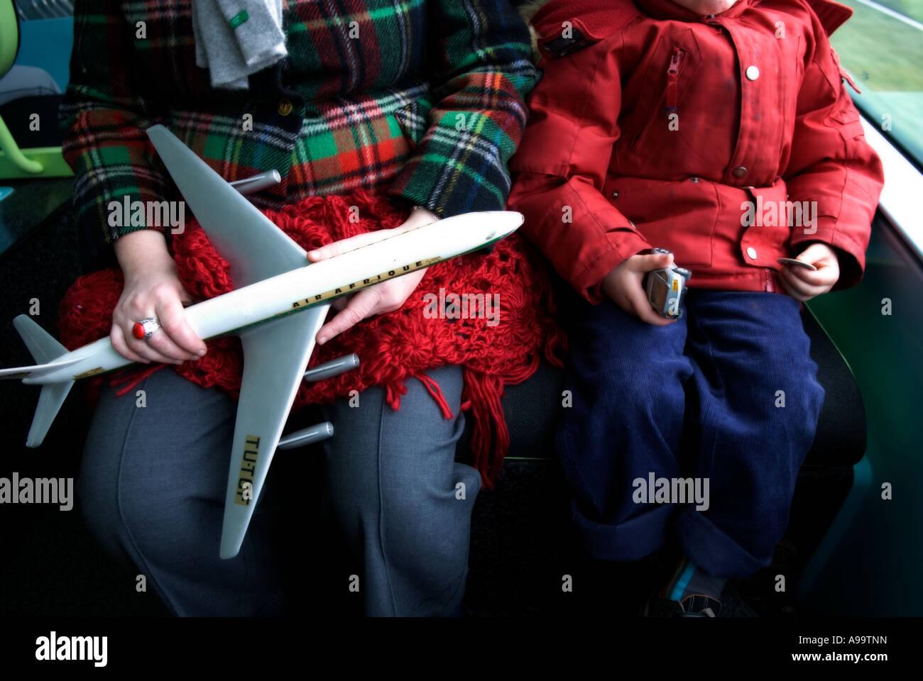 eine verkürzte Ansicht einer Mutter und ihrem Sohn ein Flugzeug und ein Auto auf den Knien halten Stockbild