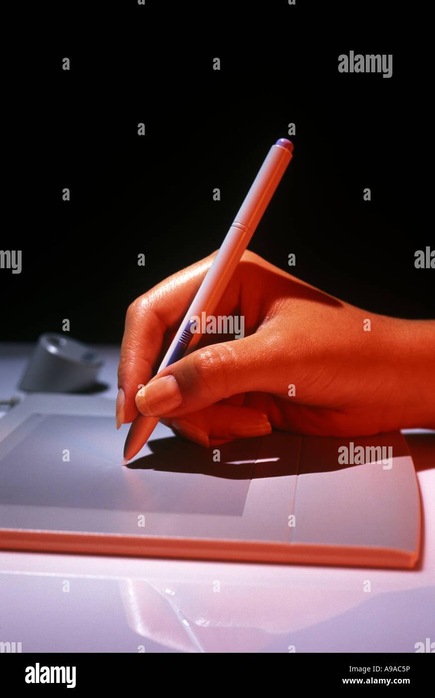 WOMANS HAND MIT GRAFIK-STIFT AUF PC-GRAFIKTABLETT Stockbild