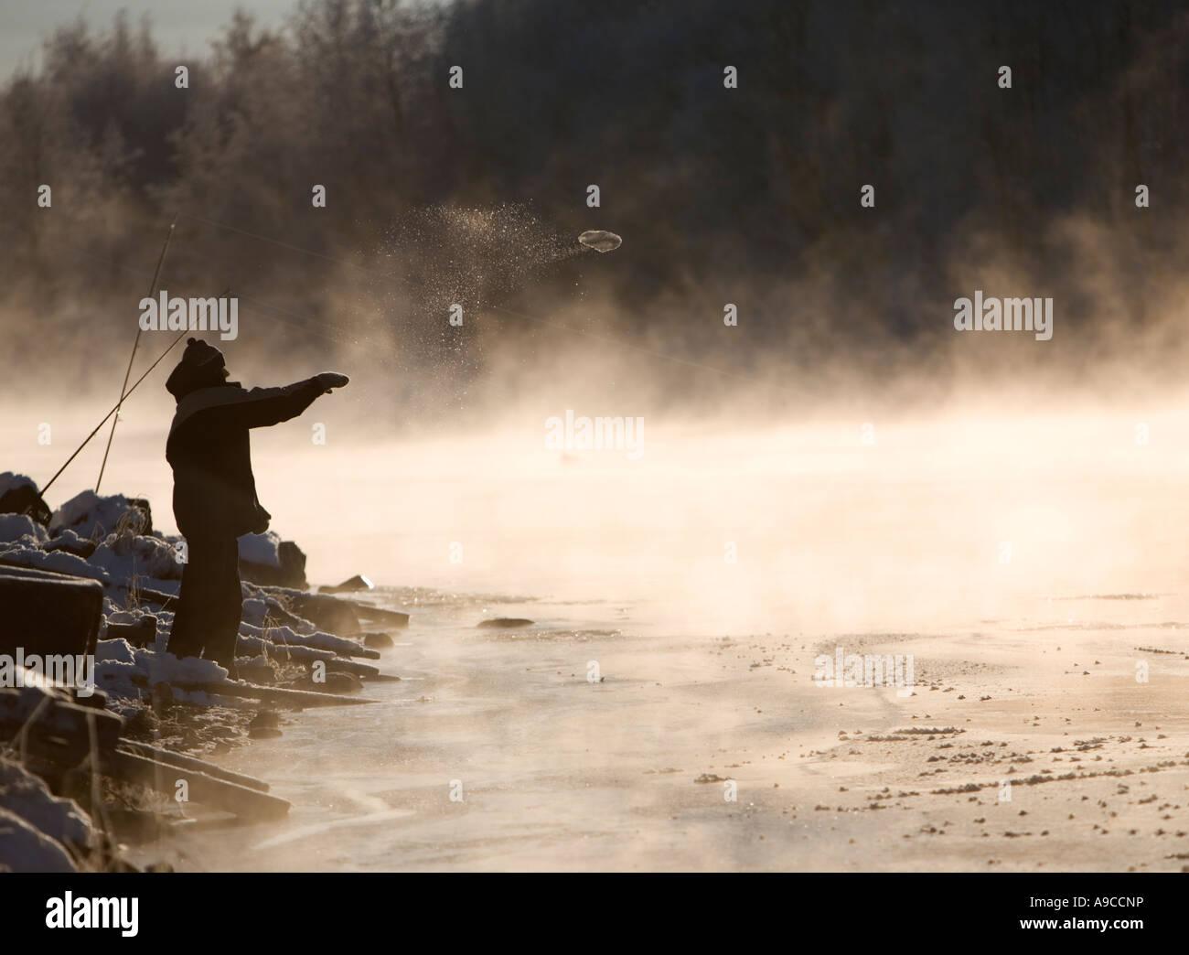 Silhouette eines Fischers im Winter, der versucht, das Eis zu brechen, durch das Werfen eines Klumpen Eis zum Eisrand, Stockbild