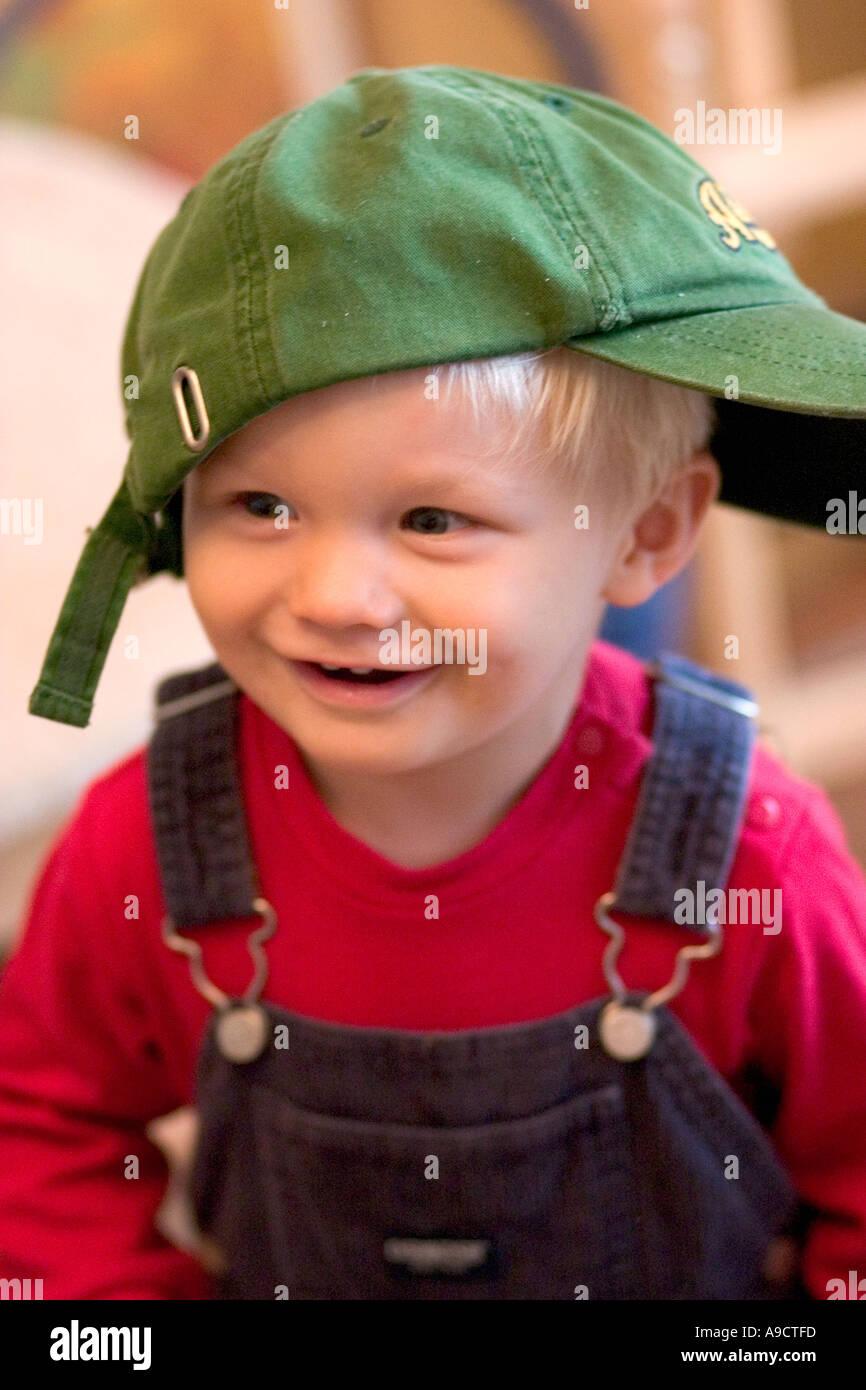 Niedlichen Kleinkind Lachen und tragen Baseball-Kappe seitlich. Lodz Polen Stockfoto