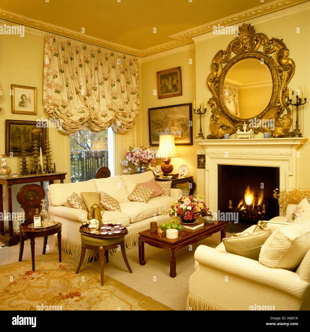 Grosse Reich Verzierte Vergoldete Spiegel Ber Kamin Mit Brennenden Feuer Im Gelben Wohnzimmer Schwalbenschwanz Blind Und Cremefarbenen Sofas