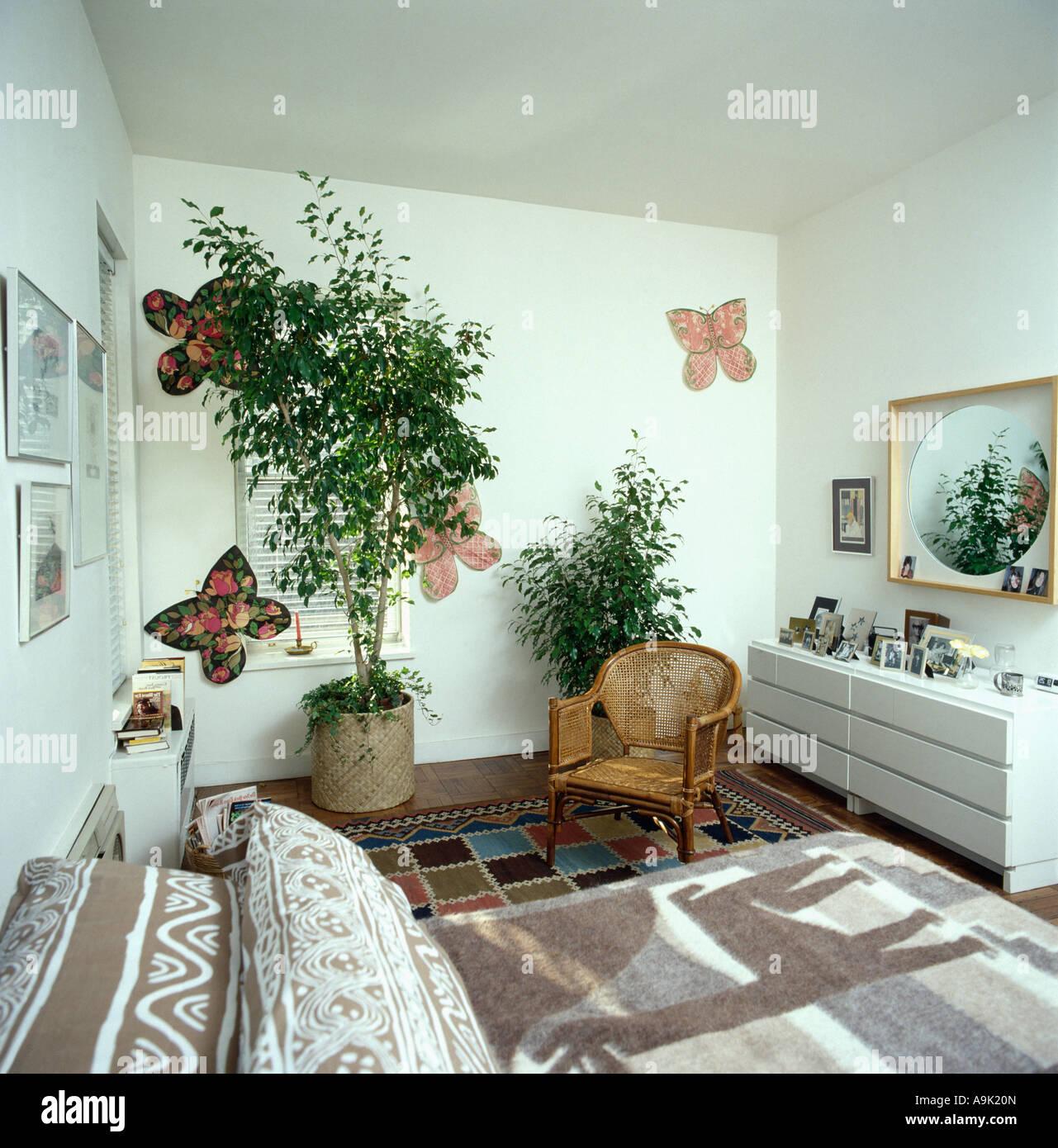 grosse zimmerpflanzen und papier schmetterlinge an der wand auf weisse achtziger jahre schlafzimmer