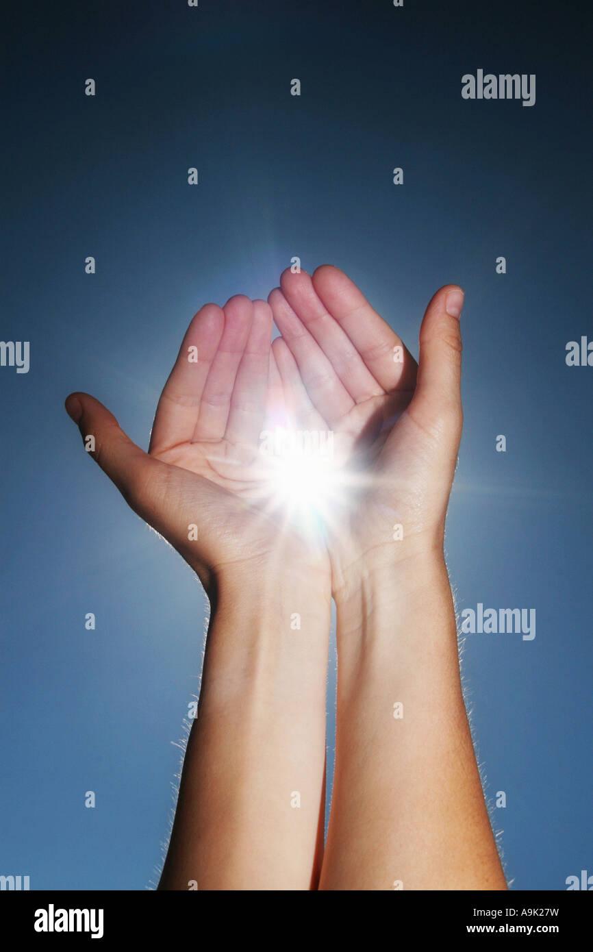 Hände halten die Sonne Stockbild