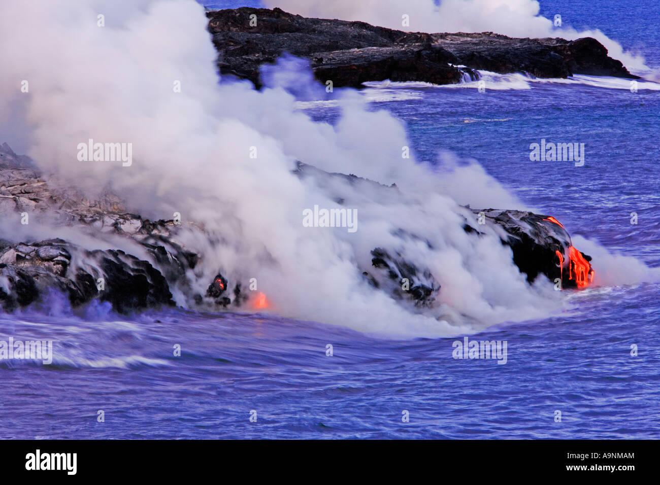 Bild der geschmolzene Lava fließt den Berg hinunter und ins Meer während Dampf steigt rund um Hawaii Volcanoes National Stockfoto
