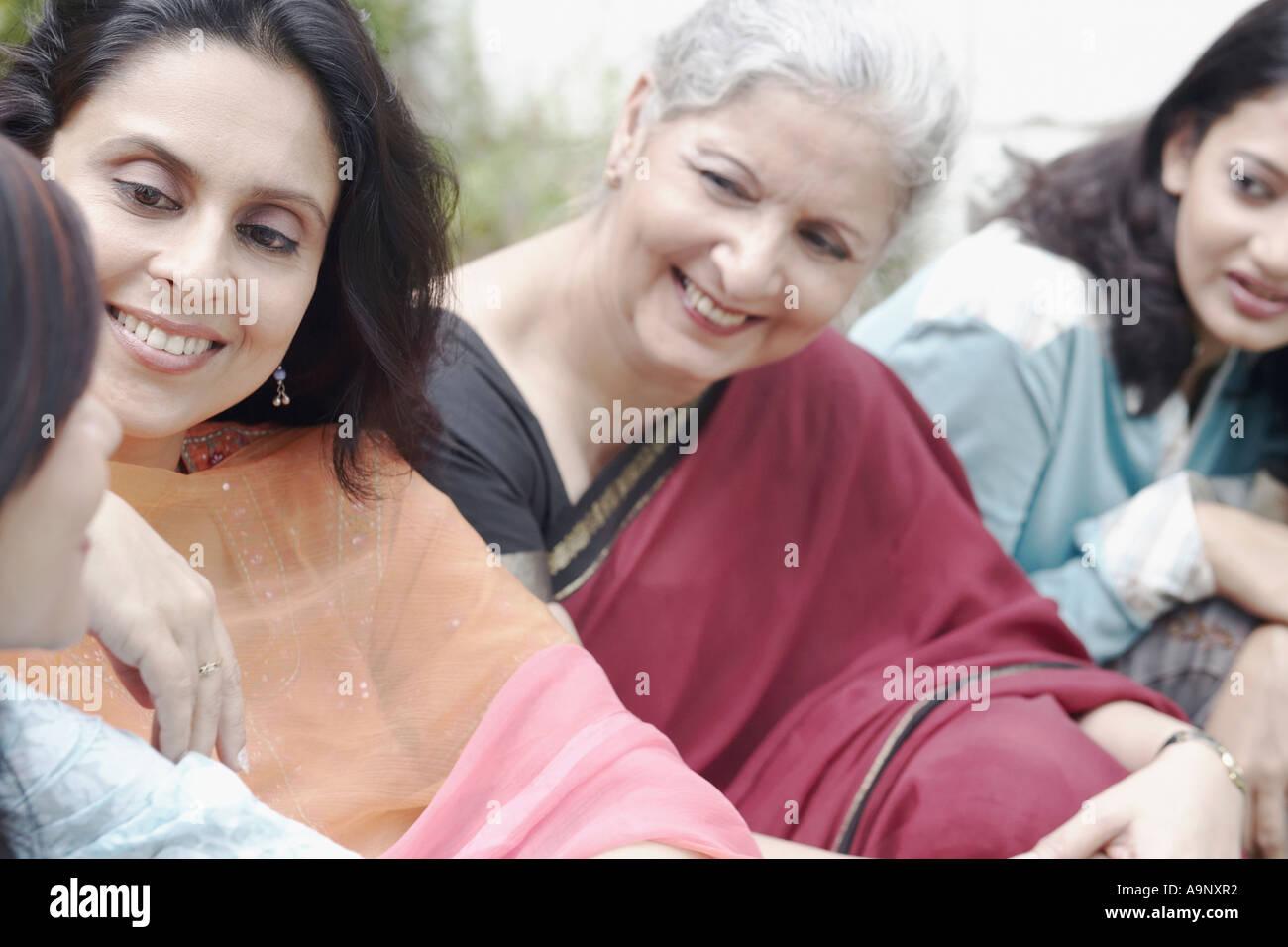 Vier Frauen sitzen gemeinsam Lächeln Stockbild