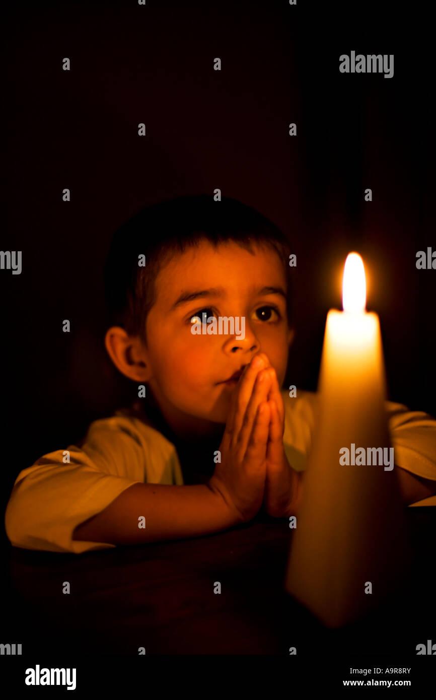 Junge betet bei Kerzenschein Stockbild