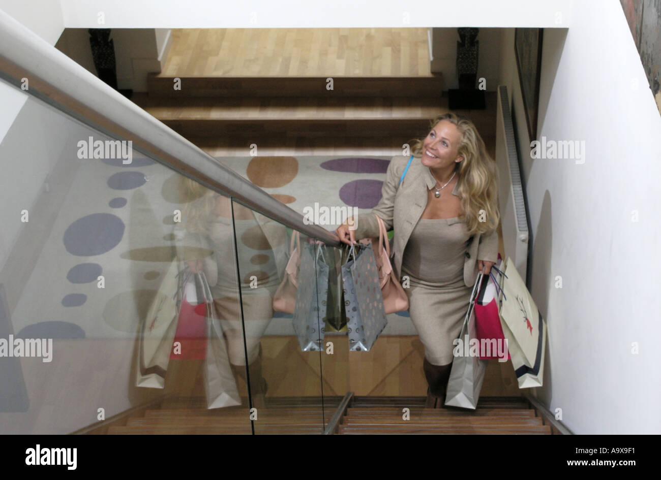 wohlhabende Frau dreißiger Jahre aufsteigende Treppe mit ihren Einkaufstüten lächelnd Stockbild