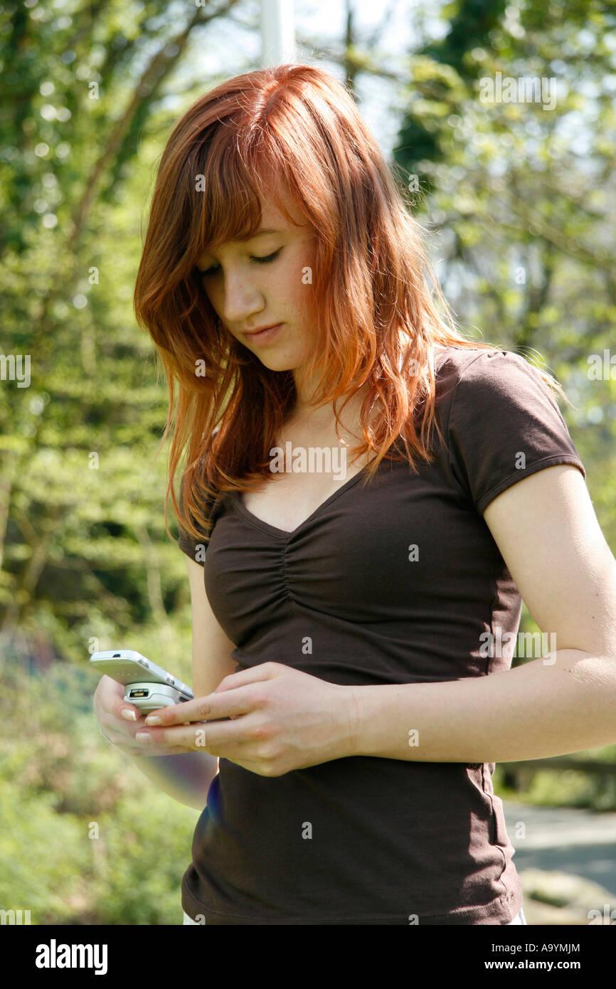 14 jahre altes m dchen mit rot gef rbten haaren mit ihrem handy spielen rund um stockfoto bild