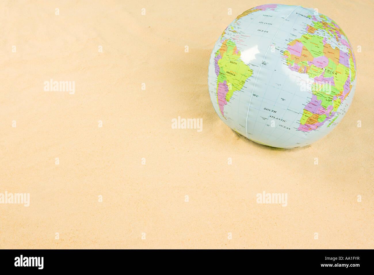 Aufblasbare Weltkugel auf Strand Stockbild