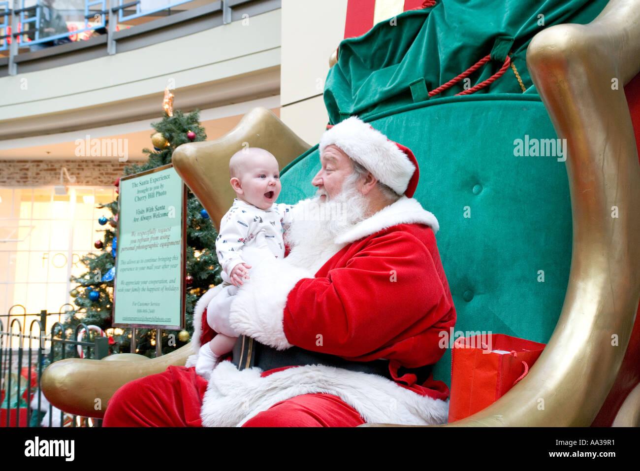 Santa Claus in einem Einkaufszentrum mit aufgeregt baby Stockbild