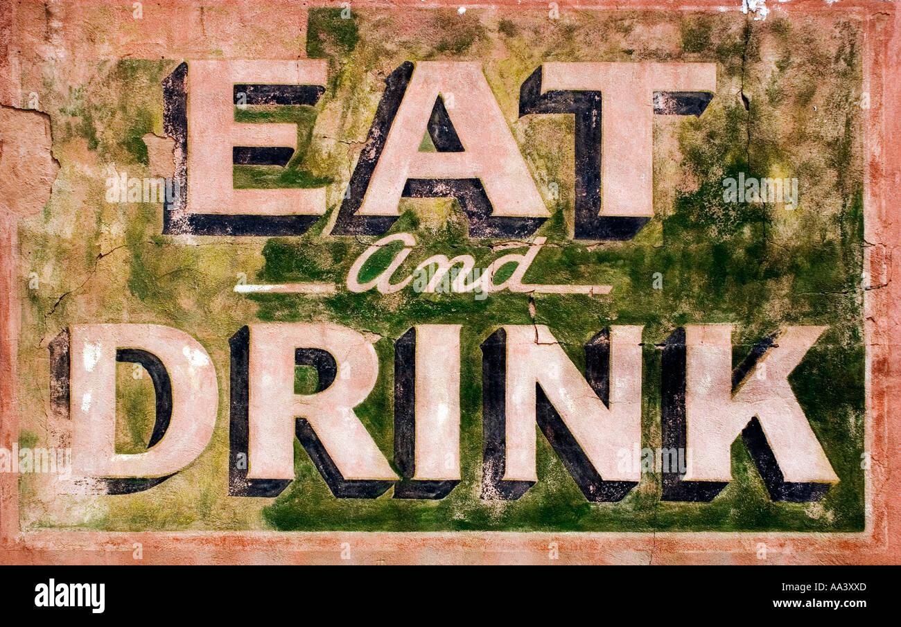 Essen Sie und trinken Sie Schild an einem alten Gebäude in Corrizozo New Mexico Stockbild