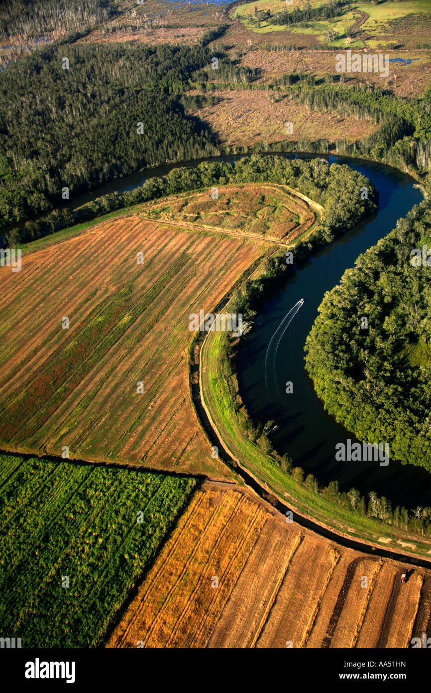 Ein Fluss schlängelt sich durch natürliche Feuchtgebiete und eine Zuckerrohr-Plantage in der Nähe Stockbild