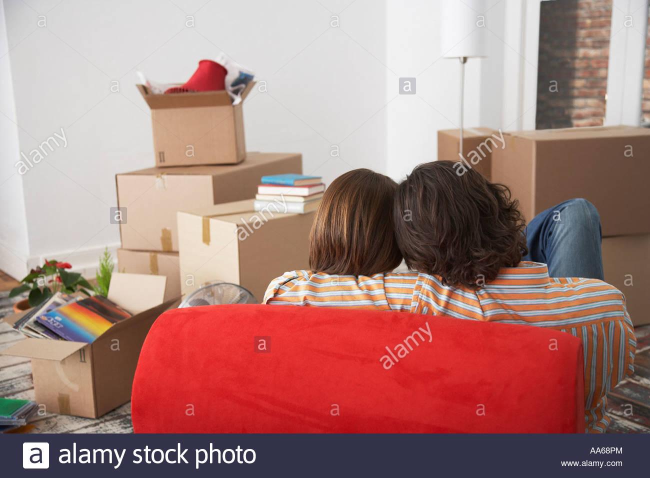 Rückansicht des Paares auf roten Stuhl im Haus mit Kartons Stockbild