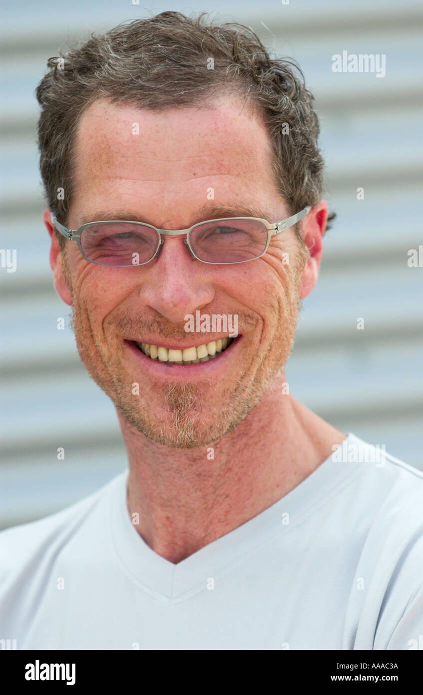 Bespeckled kaukasischer Mann in seinen 40ern Lächeln in die Kamera Stockbild